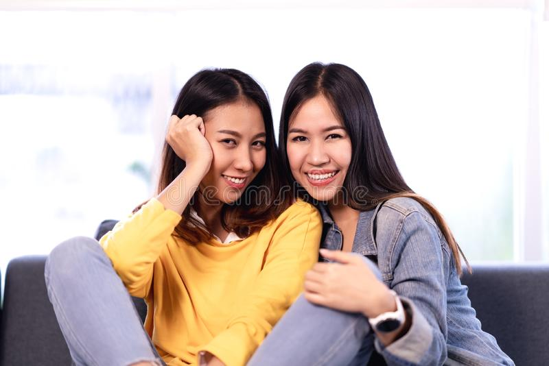 Young attractive asian girlfriends sitting together at couch sofa at home smiling and looking at camera stock photography