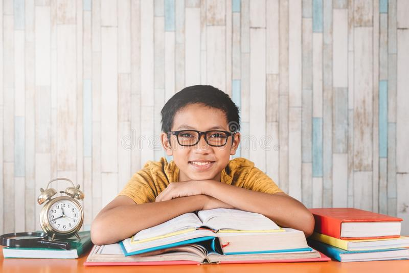 Young attractive asian male student smiling while looking at camera sitting against table with books stock image
