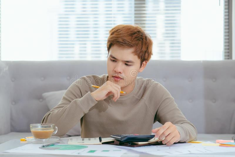 Young attractive Young Asian man at home sitting on sofa with calculator accounting costs, charges, taxes and mortgage for paying royalty free stock photo