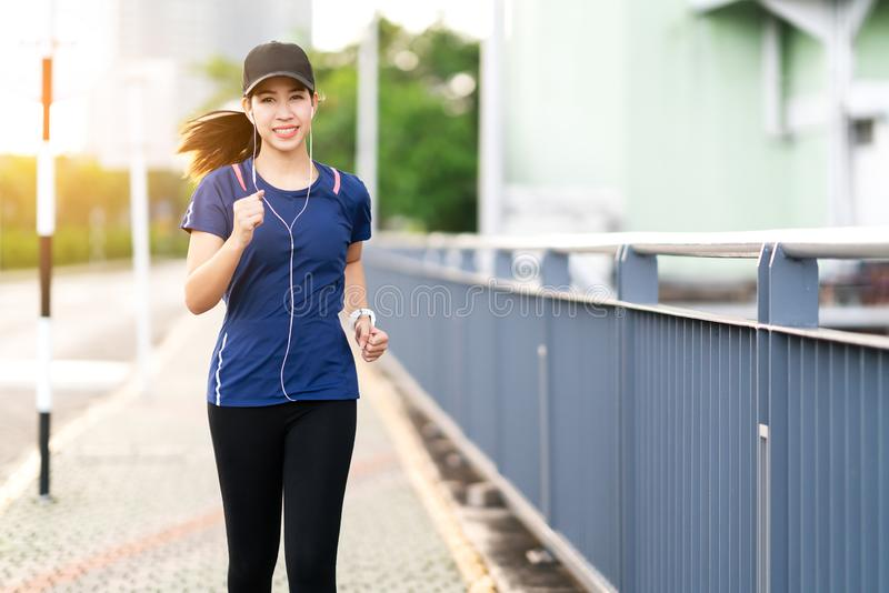 Young attractive asian runner woman running in city street or foot path way listen to music royalty free stock photos