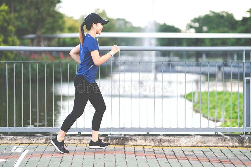 Young attractive asian runner woman running at sidewalk way in public nature city park with lake water royalty free stock photography
