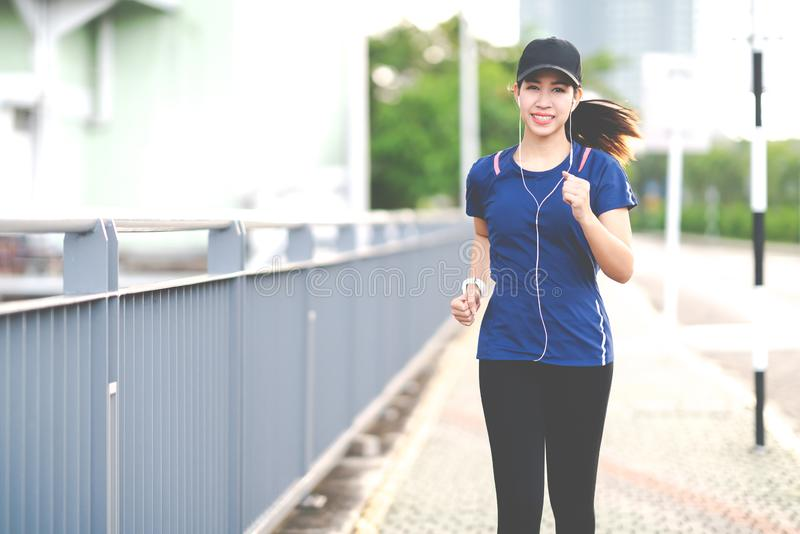 Young attractive asian runner woman running in urban city street or foot path way listen to music wearing blue or black sporty royalty free stock photos