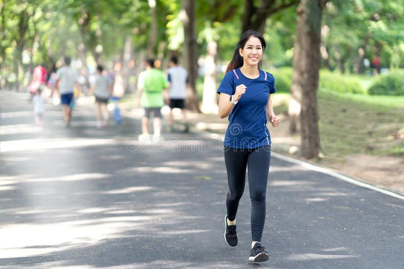 Young attractive asian runner woman running in urban public nature park in city royalty free stock photos