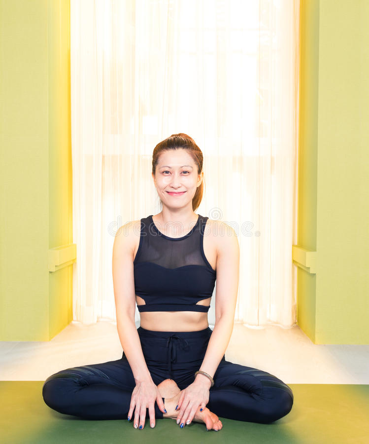 young attractive asian woman in black yoga exercise outfit sitting and smiling at home, bathed warm light from the window stock image