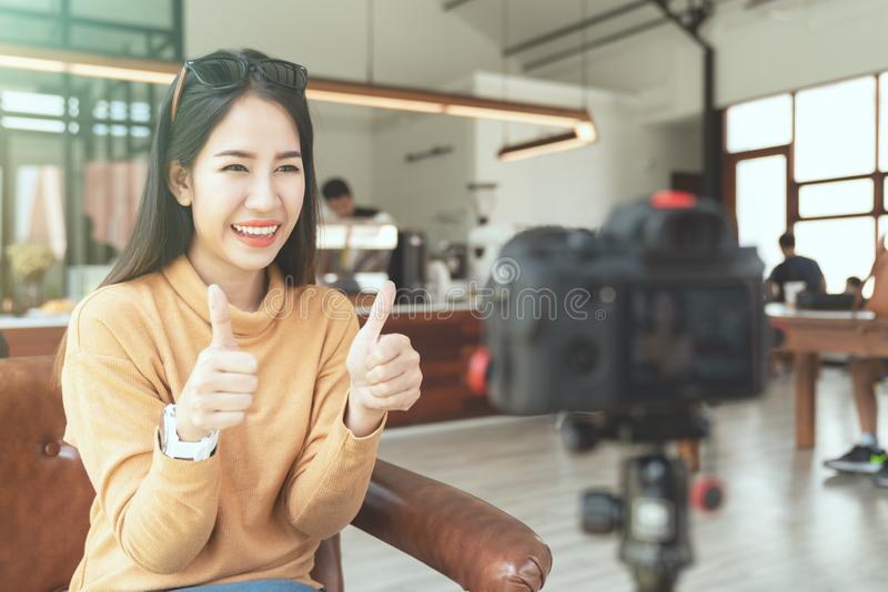 Young attractive asian woman blogger or vlogger looking at camera and talking on video shooting at cafe coffee shop. stock images