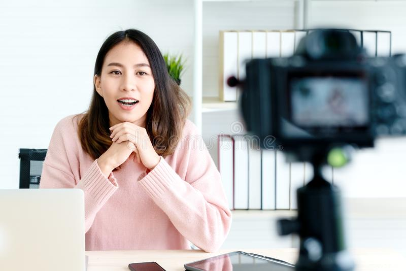 Young attractive asian woman blogger or vlogger looking at camera and talking on video shooting with technology. Social media stock photos