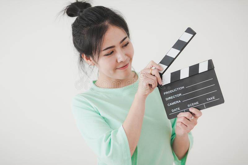 Young Asian woman playing clapperboard with positive emotion. Young attractive Asian woman holding clapperboard with positive feeling. Film production and movie royalty free stock photo