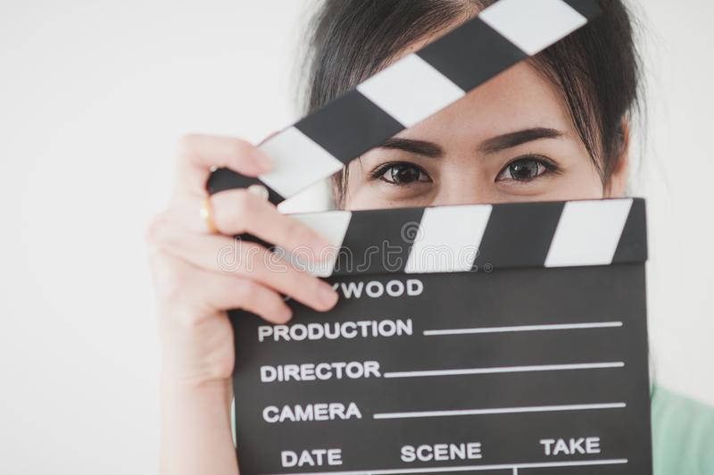 Young Asian woman playing clapperboard with positive emotion. Young attractive Asian woman holding clapperboard with positive feeling. Film production and movie stock photo
