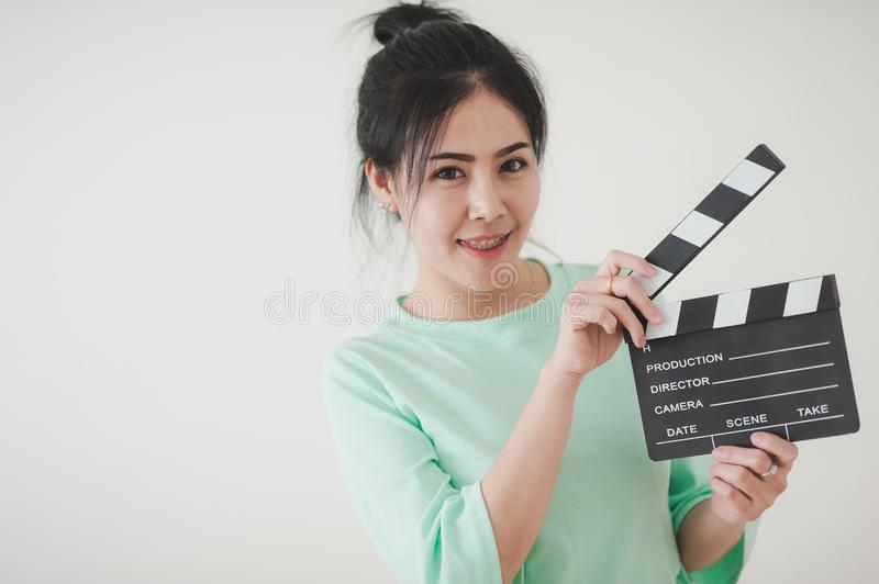 Young Asian woman playing clapperboard with positive emotion. Young attractive Asian woman holding clapperboard with positive feeling. Film production and movie royalty free stock image