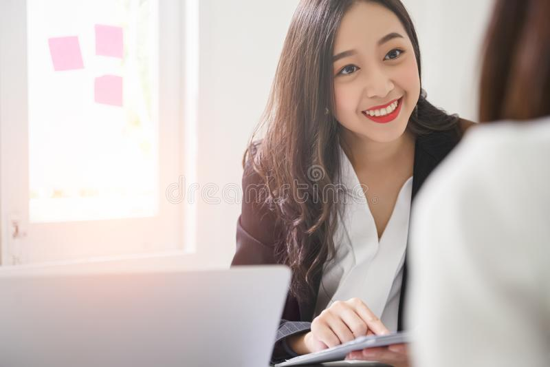 A young attractive asian woman is interviewing for a job. Her interviewers are diverse. stock images