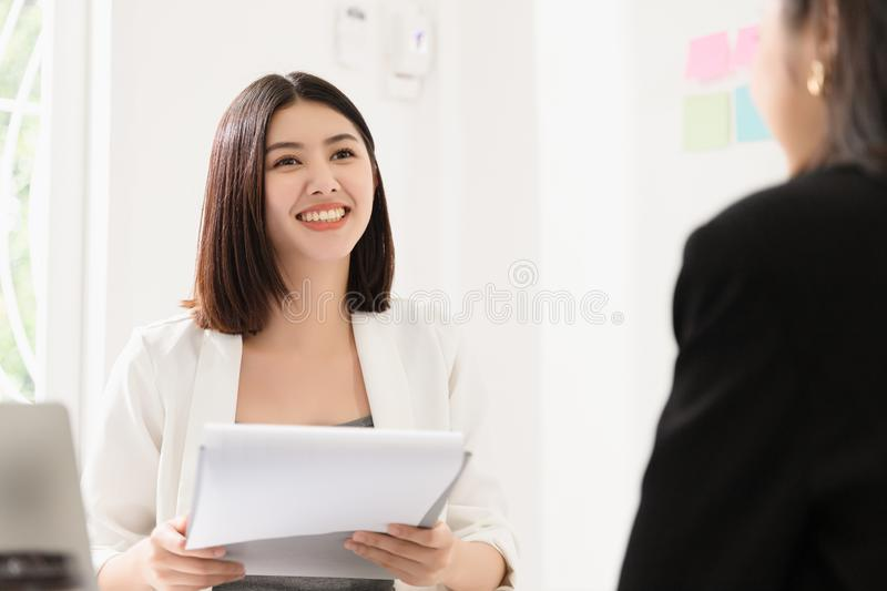 A young attractive asian woman is interviewing for a job. Her interviewers are diverse. royalty free stock photo