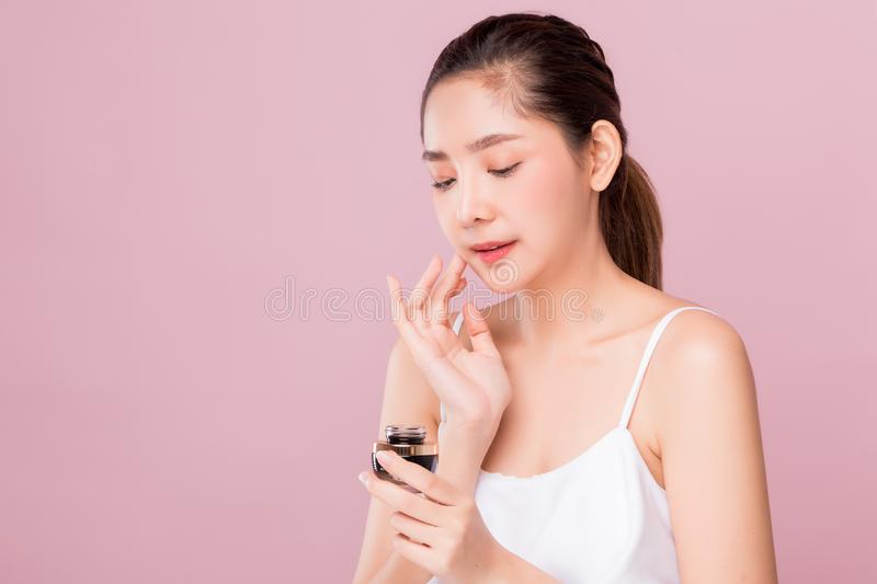 Young attractive Asian woman with perfect healthy skin holding facial cream isolated on pink royalty free stock photos