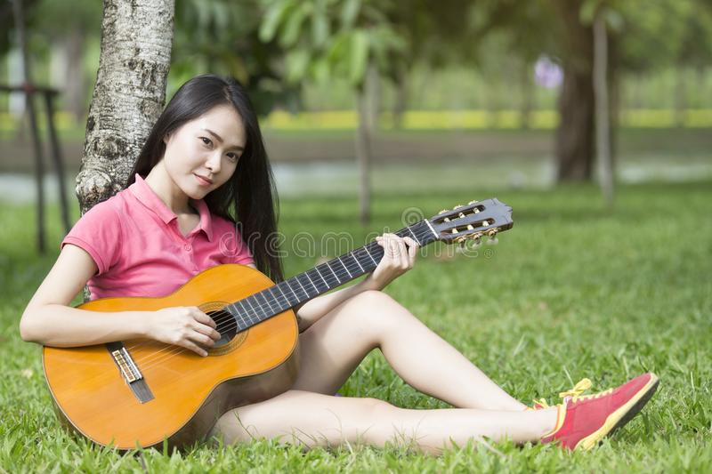 Young attractive asian woman playing acoustic guitar royalty free stock photos