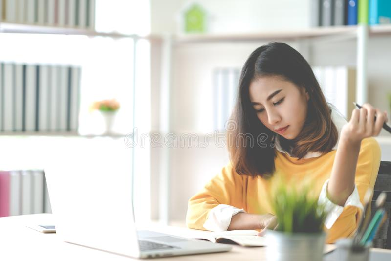 Young attractive asian woman or student working on thesis assignment or studying online in self e-learning education program. stock images