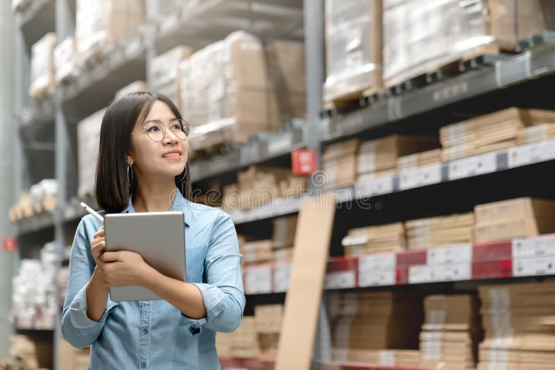 Young attractive asian worker, owner, entrepreneur woman holding smart tablet computer looking side up above shelf with royalty free stock image