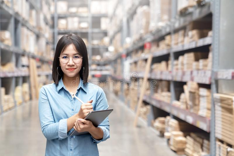 Young attractive asian worker, owner, entrepreneur woman holding smart tablet looking at camera with concept efulfillment service stock images