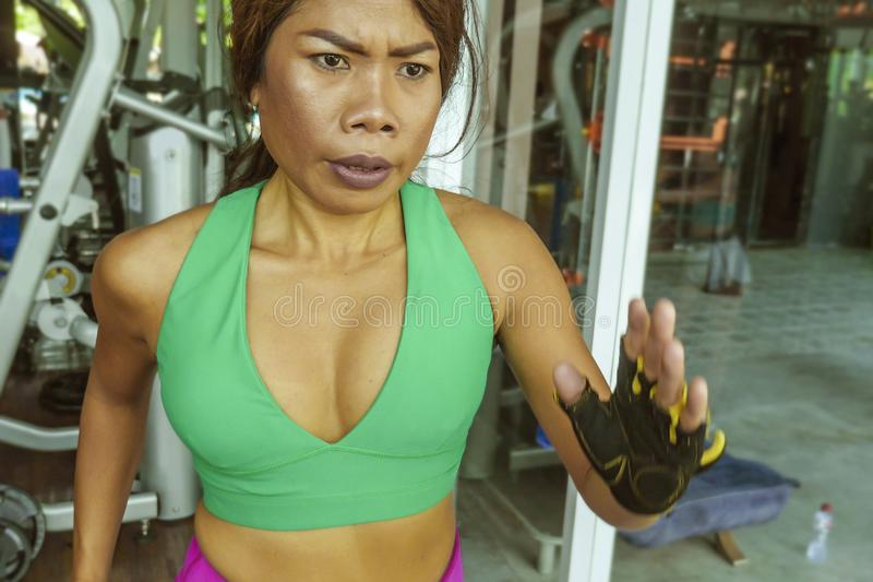 Young attractive and athletic Asian Indonesian sport woman running on treadmill at gym fitness club training hard jogging workout stock photo