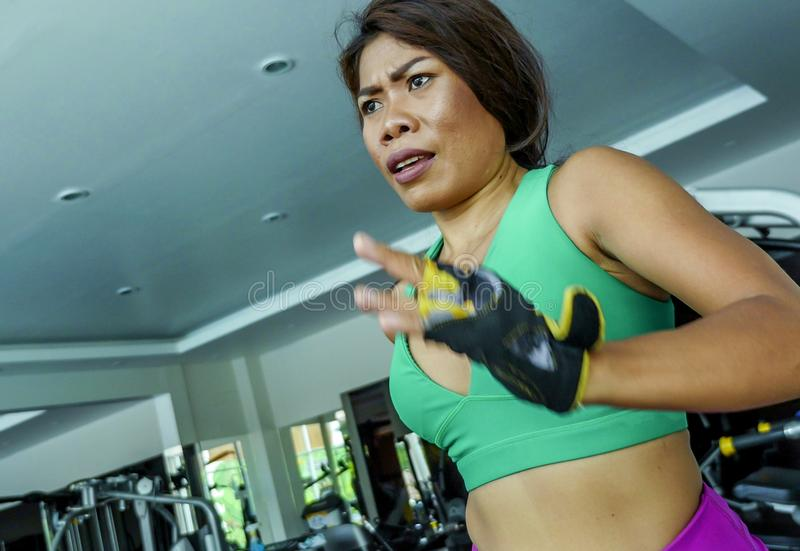 Young attractive and athletic Asian Indonesian sport woman running on treadmill at gym fitness club training hard jogging workout stock images
