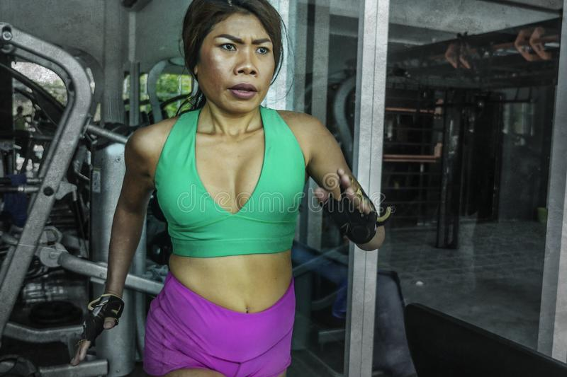 Young attractive and athletic Asian Indonesian sport woman running on treadmill at gym fitness club training hard jogging workout royalty free stock photos