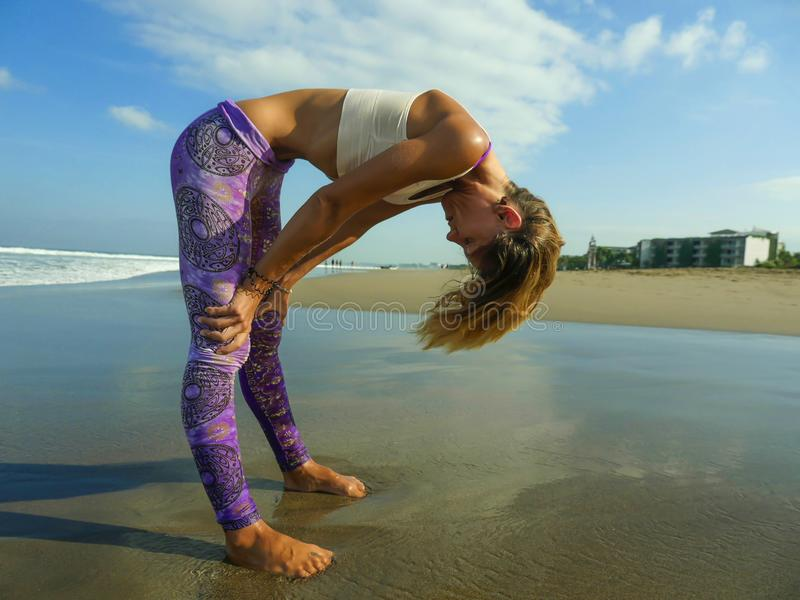 Young attractive and athletic skinny woman doing yoga stomach breathing exercise concentrated and focused at beautiful beach in. Body control relaxation and stock photos