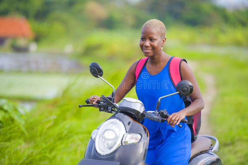 Young attractive backpacker tourist afro American black woman riding motorbike happy in beautiful Asia countryside along green ric. Young attractive and happy royalty free stock image