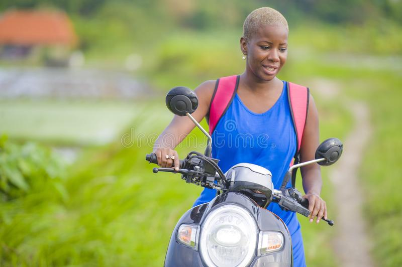 Young attractive backpacker tourist afro American black woman riding motorbike happy in beautiful Asia countryside along green ric. Young attractive backpacker stock photo