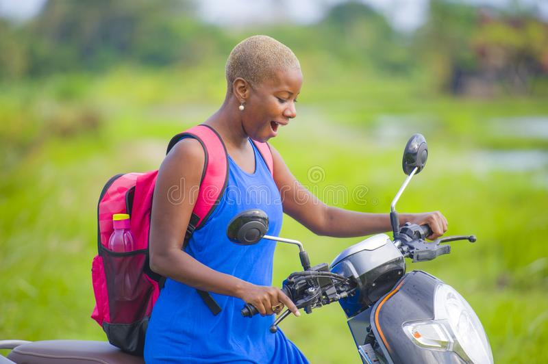 Young attractive backpacker tourist afro American black woman riding motorbike happy in beautiful Asia countryside along green ric. Young attractive backpacker royalty free stock photo