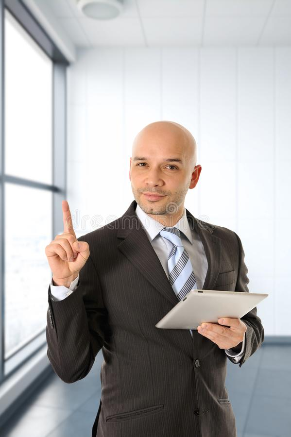 Young attractive bald Latin business man in suit and necktie pointing with finger holding digital tablet computer stock photography