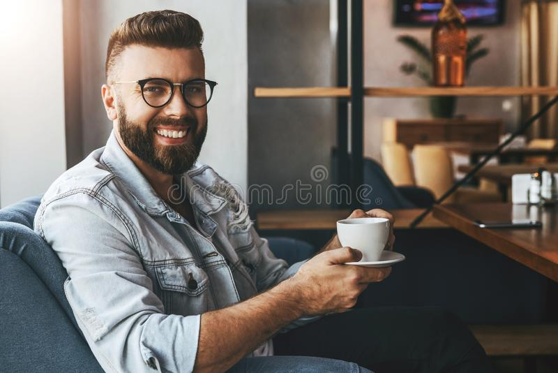 Young attractive bearded businessman in trendy glasses sits in cafe,drinks coffee during lunch time,rests,enjoys drink stock photography