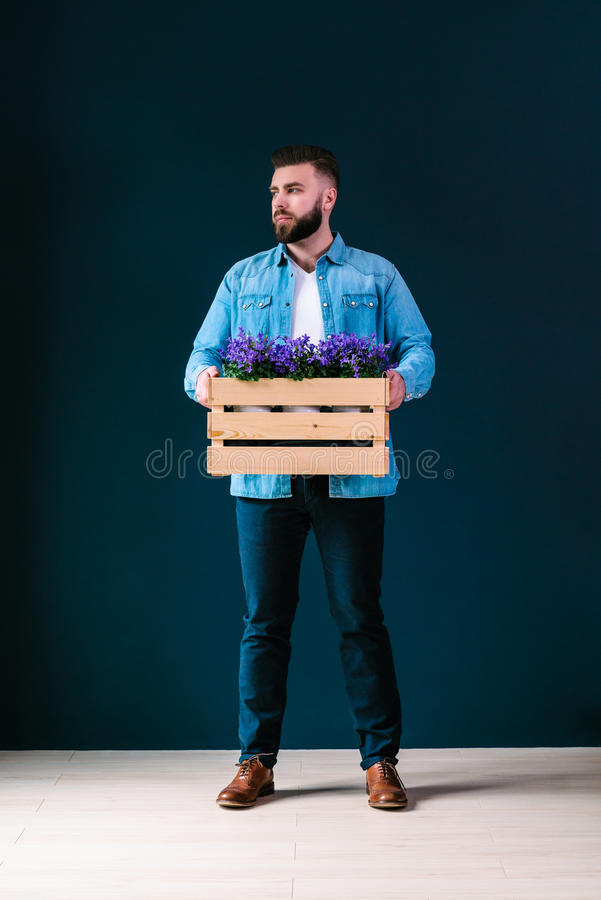Young attractive bearded hipster man with brunette hair,wearing in denim shirt and white t-shirt stands indoors,holding wooden box stock photos