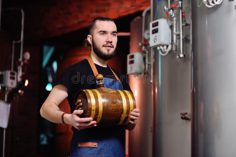 Attractive bearded man with a wooden barrel of wine or beer. Young attractive bearded man with a wooden barrel of wine or beer royalty free stock photo