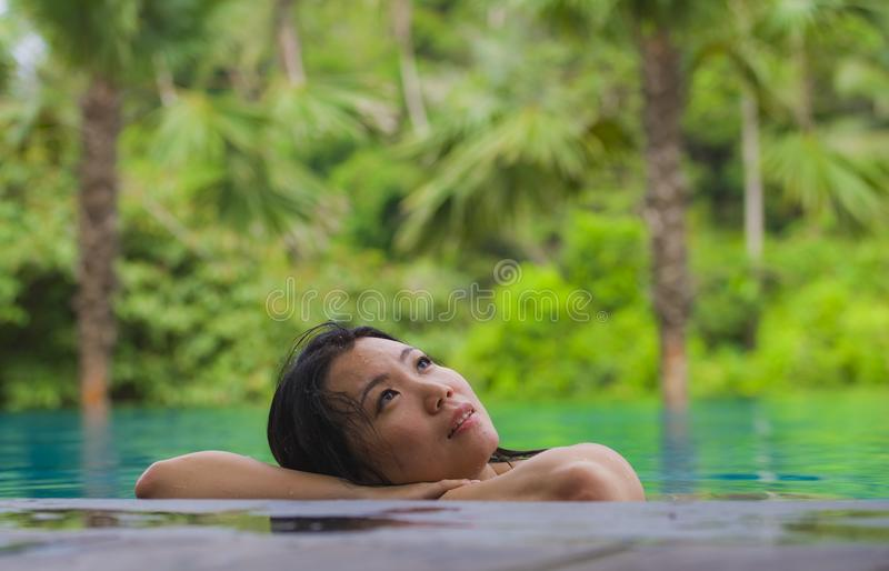 Young attractive and beautiful Asian Chinese woman relaxing happy at tropical beach resort swimming at jungle infinity pool royalty free stock images