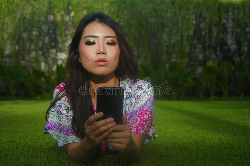 Young attractive beautiful and gorgeous Asian Chinese woman lying on green grass park using internet social media app on mobile ph royalty free stock images