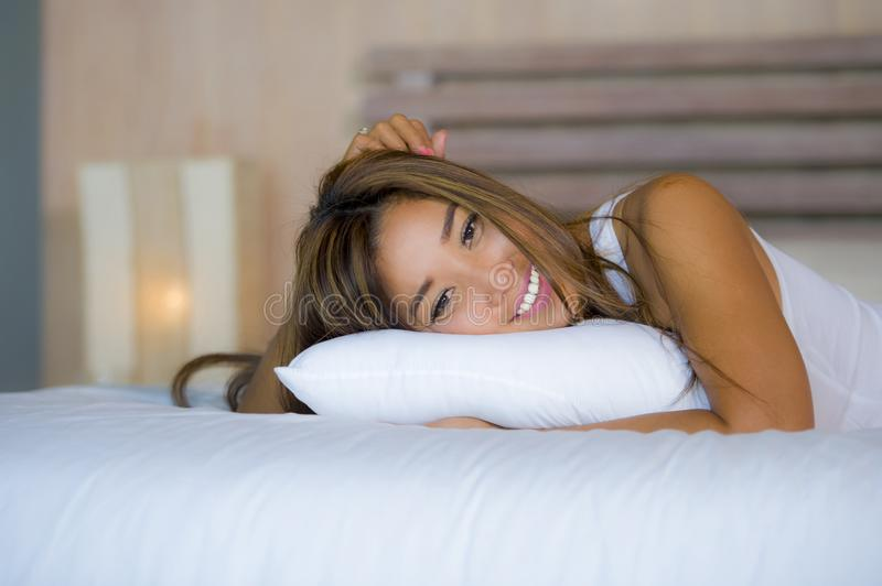 Young attractive beautiful and happy Asian Latin mixed woman lying on bed at home bedroom posing relaxed and smiling cheerful royalty free stock photo