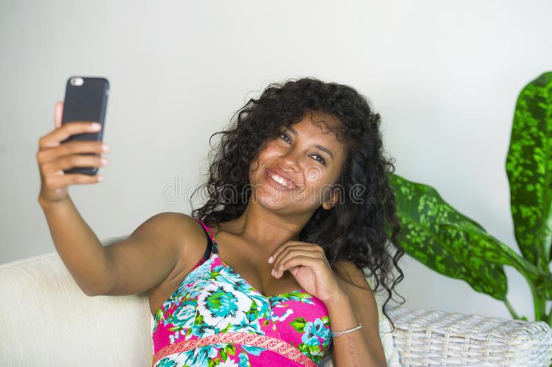 Young attractive and beautiful happy black latin American woman taking selfie portrait picture with mobile phone at holidays apart. Ment in internet social media stock photos
