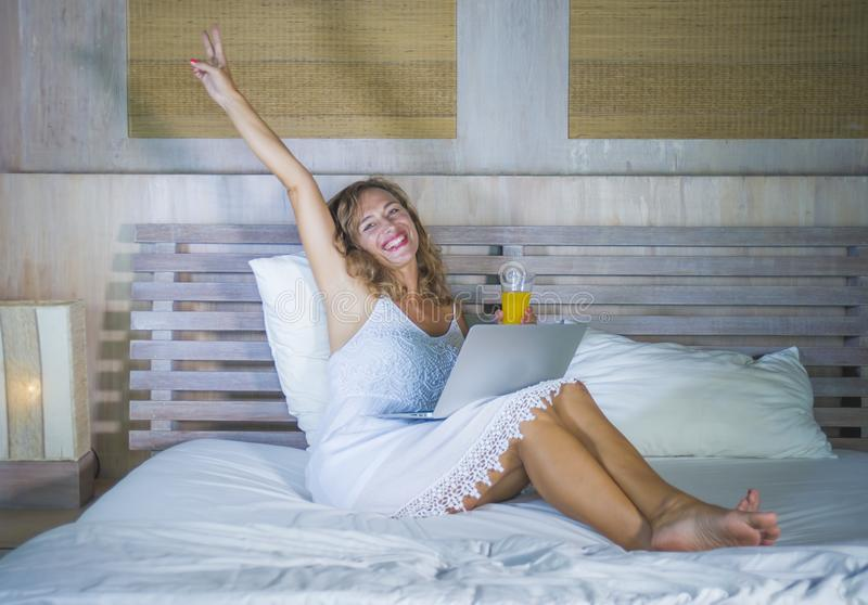 Young attractive and beautiful happy Caucasian woman 30s lying in bed at home using internet working on computer laptop smiling re royalty free stock photography