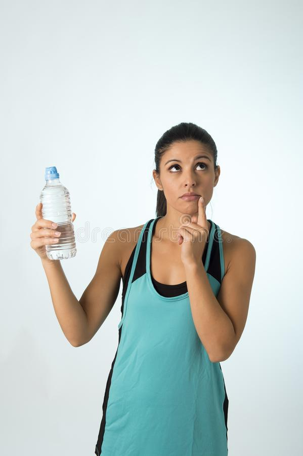 Young attractive and beautiful Latin sport woman holding water of bottle thinking if drinking more stock images