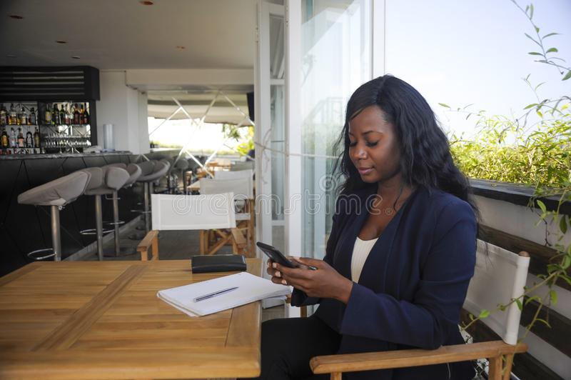 Young attractive black African American woman sitting outdoors at coffee shop working busy and happy. With internet mobile phone texting in entrepreneur and stock photo