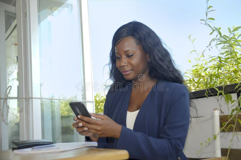 Young attractive black African American woman sitting outdoors at coffee shop working busy and happy. With internet mobile phone texting in entrepreneur and stock photos