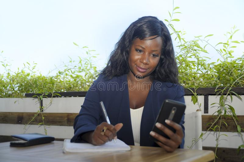 Young attractive black African American woman sitting outdoors at coffee shop working busy and happy. With internet mobile phone texting in entrepreneur and royalty free stock images