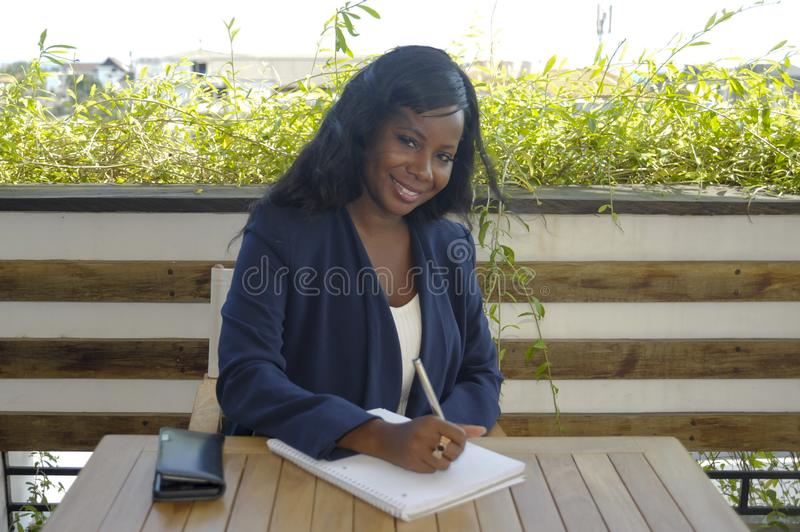 Young attractive black African American woman sitting outdoors at coffee shop working busy and happy. With pen notepad and mobile phone in entrepreneur and royalty free stock photos