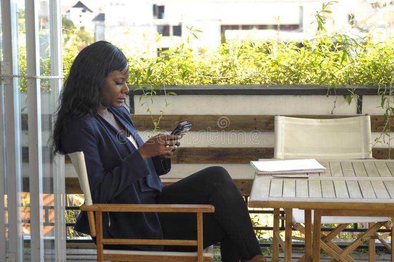 Young attractive black African American woman sitting outdoors at coffee shop working busy and happy. With pen notepad and mobile phone in entrepreneur and royalty free stock image