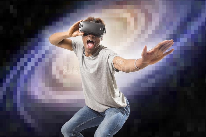 Young attractive black afro American man using vr virtual reality 3D goggles playing space travel videogame with pixelated compute stock photography