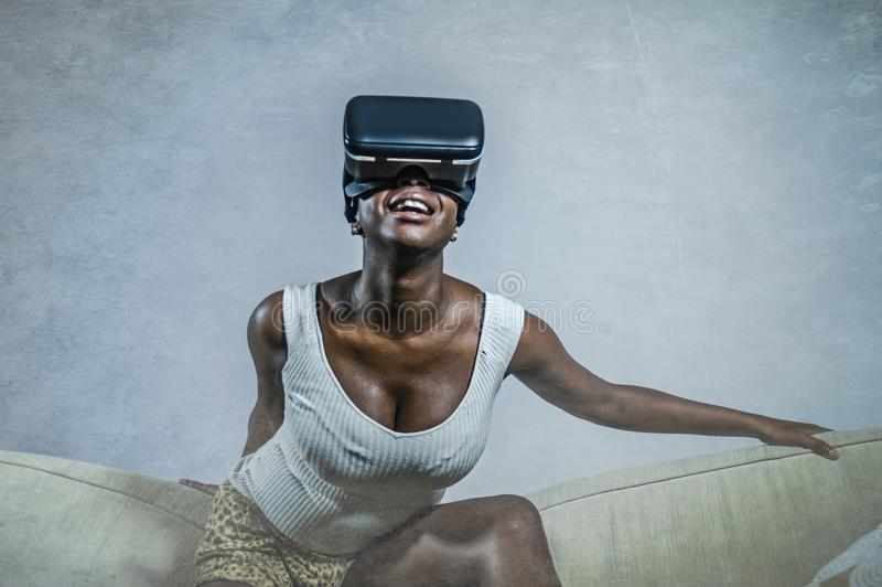 Young attractive black afro American woman playing VR goggles headset trying to touch illusion at living room couch royalty free stock photography