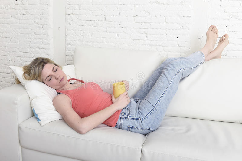 Young attractive blond hair woman holding cup of coffee lying on sofa couch at home living room sleeping relaxed stock photography