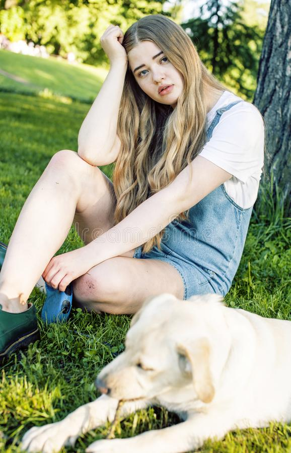 Young attractive blond woman playing with her dog in green park at summer, lifestyle people concept. Young attractive blond real fat woman playing with her dog stock photography