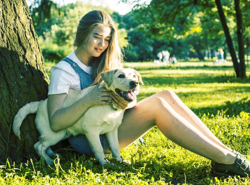 Young attractive blond woman playing with her dog in green park at summer, lifestyle people concept. Young attractive blond real fat woman playing with her dog royalty free stock photos