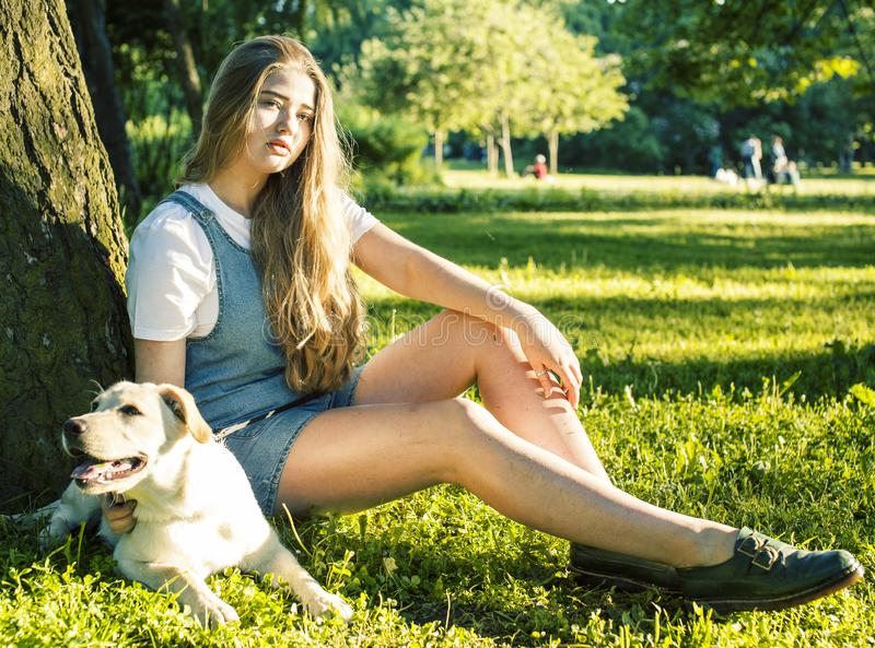 Young attractive blond woman playing with her dog in green park at summer, lifestyle people concept. Young attractive blond real fat woman playing with her dog stock images