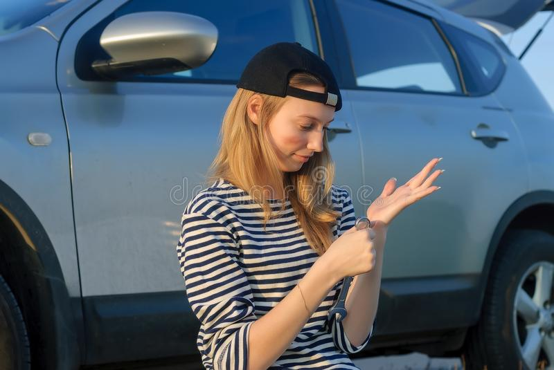 Young Blond Woman with wrench near car royalty free stock photo