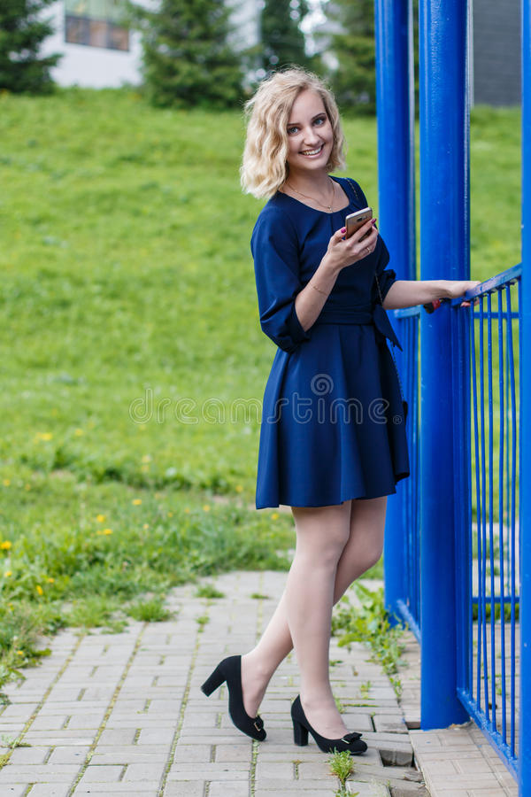 Young attractive blond woman in a summer park stock photo